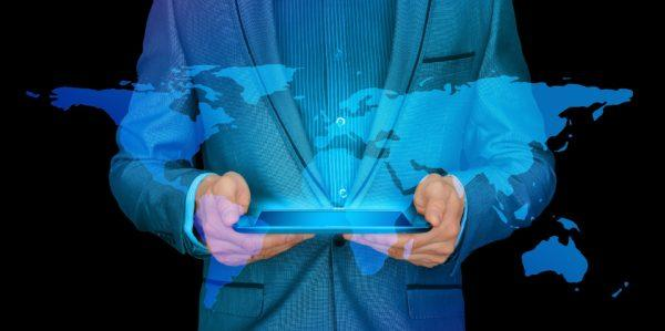 business man holding a tablet reflecting world map